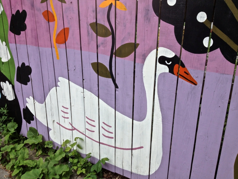 White Swan painted on pink and purple fence