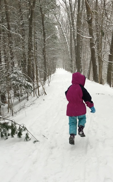 child skipping along wooded path